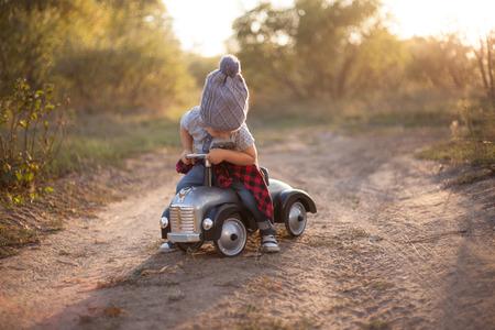 Photo pour Toddler driving toy car outdoors - image libre de droit
