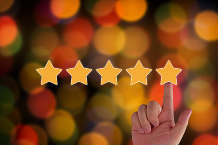 Photo pour Rating and evaluation concept.  hand and five yellow star on blur background - image libre de droit
