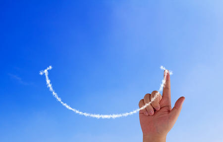 Foto de Happiness concept, hand drawing smile cloud on blue sky background - Imagen libre de derechos