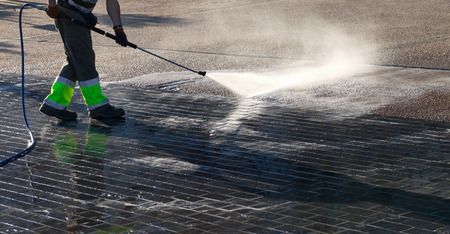 Foto per Wet cleaning of street with pressurized water. - Immagine Royalty Free