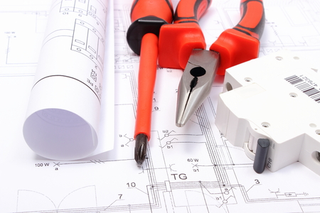 Foto de Rolled electrical diagrams, electric fuse and work tools lying on construction drawing of house, drawings for the projects engineer jobs - Imagen libre de derechos
