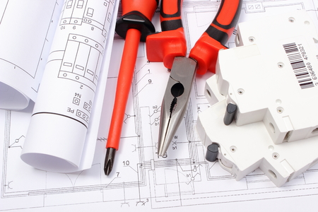 Photo pour Rolled electrical diagrams, electric fuse and work tools lying on construction drawing of house, drawings for the projects engineer jobs - image libre de droit