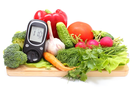 Foto per Glucose meter and fresh ripe raw vegetables lying on wooden cutting board, desk of healthy organic vegetables, concept for healthy eating and diabetes. Isolated on white background - Immagine Royalty Free