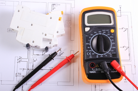Photo pour Multimeter with cables and electric fuse lying on construction drawing of house, electrical drawings and tools for engineer jobs - image libre de droit