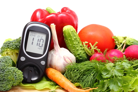 Foto per Glucose meter and fresh ripe raw vegetables lying on wooden cutting board - Immagine Royalty Free