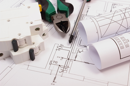 Foto de Metal pliers, screwdriver, electric fuse and rolls of diagrams on electrical construction drawing of house, work tool and drawing for projects engineer jobs - Imagen libre de derechos