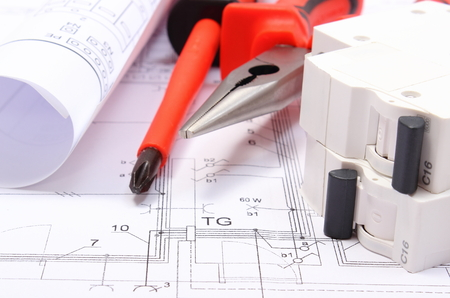 Foto de Rolls of electrical diagrams, electric fuse and work tools lying on construction drawing of house, drawings for the projects engineer jobs - Imagen libre de derechos