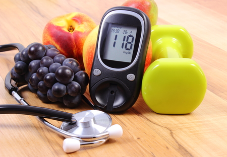 Foto de Glucose meter with medical stethoscope, fruits and dumbbells for using in fitness, concept of diabetes, healthy lifestyles and nutrition - Imagen libre de derechos