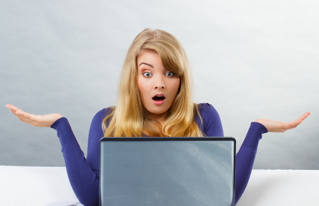 Foto de Frustrated and scared woman shrugging shoulders with raised hands sitting on sofa and looking at laptop screen, computer problem - Imagen libre de derechos