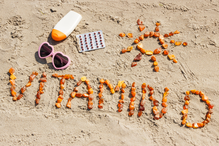 Foto de Medical pills, inscription vitamin D made of amber stones and accessories for sunbathing on sand at beach, concept of vacation time and prevention of vitamin D deficiency - Imagen libre de derechos