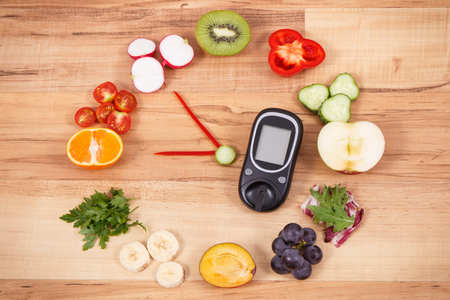 Foto per Glucometer for checking sugar level and clock made of fruits and vegetables, healthy breakfast for diabetics concept - Immagine Royalty Free