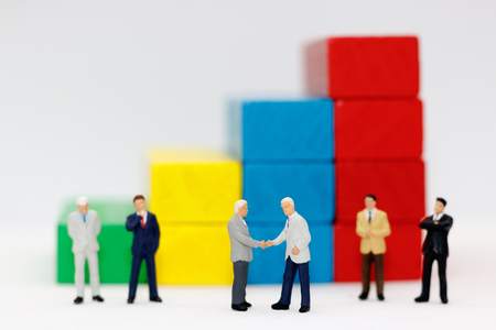 Photo for Miniature people handshake with step of Wood block stack.  agreement, investment, partnership and business concept - Royalty Free Image
