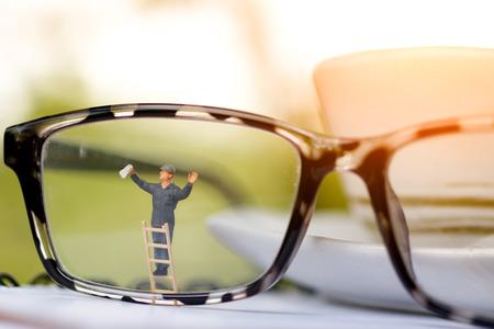 Photo pour Miniature people worker cleaning eyes glasses. Business concept - image libre de droit