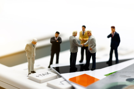 Photo pour Miniature people, businessman businessman handshake on tax button of calculator,  Commitment, agreement, investment and partnership concept - image libre de droit