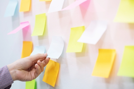 Foto de close up hand people business man sticky notes notes in the wall at meeting room. Sticky note paper reminder schedule board. Colorful variety copy empty space. soft focus. - Imagen libre de derechos