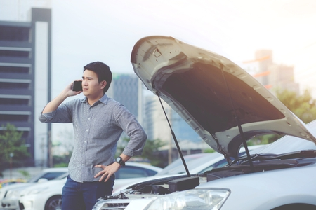 Photo pour Angry man stand in front a broken car calling for assistance phone. - image libre de droit