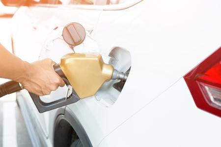 Photo pour Man handle refilling the car with fuel at the refuel station - image libre de droit