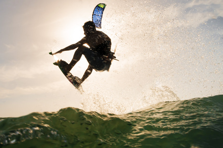 Photo pour Backlight of a surfer jumping over the ocean water in front of the sunset - image libre de droit