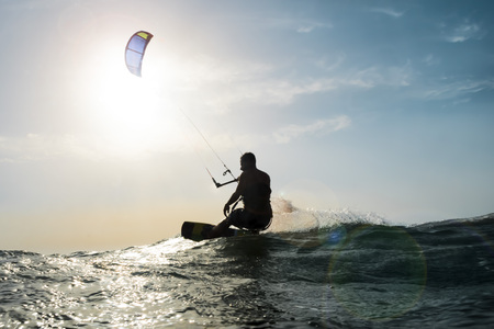 Photo pour Silhouette of a kite surfer surfing the sea in front of the sunset - image libre de droit