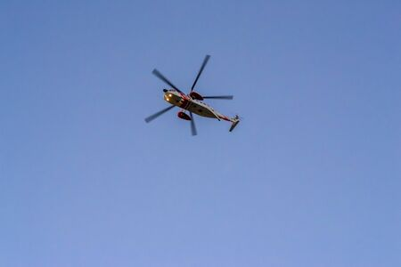 Foto de horizontal photograph of a blue sky, when it begins to get dark, in which the sea rescue helicopter stands out, flying over us, in an emergency looking to help people - Imagen libre de derechos