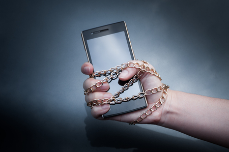 Photo pour Lock chain smartphone hand woman holding ,Information security,Personal data security and protection concept - metal chain link hand with locked padlock on smartphone on dark background - image libre de droit