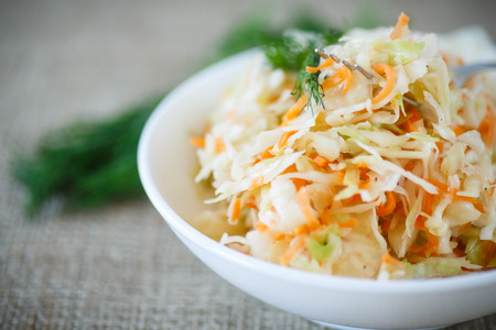 Photo pour pickled cabbage and carrots in a white plate on the table - image libre de droit