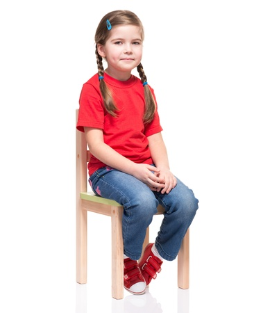 Photo for little girl wearing red t-short and posing on chair on white background - Royalty Free Image