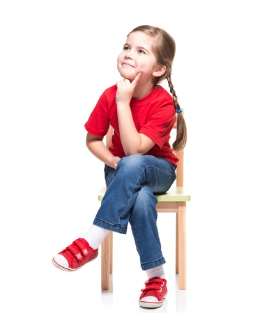 Photo pour little girl wearing red t-short and posing on chair on white background - image libre de droit