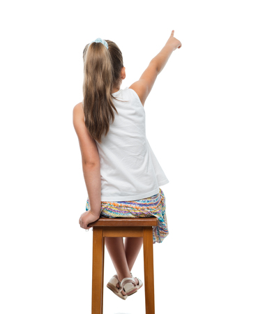 Photo pour little girl sitting on chair and pointing aside - image libre de droit