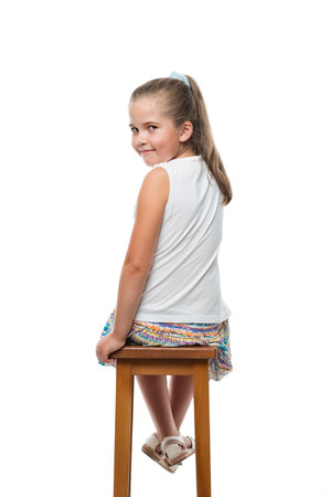 Photo pour back view of little girl sitting on chair looking back to the camera - image libre de droit