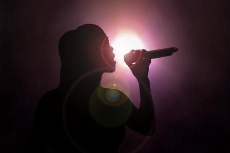 Photo for Women singing under spotlight - Royalty Free Image