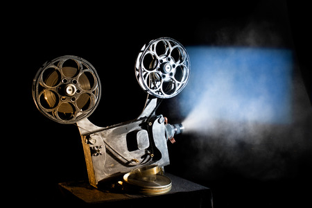 Photo pour Movie projector with the film on the black background - image libre de droit