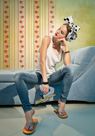 Photo pour Beautiful girl with a spatula sits on the couch near the wall with a wallpaper - image libre de droit