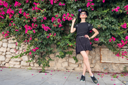 Foto de Slim girl outdoors surrounded by flowering plants - Imagen libre de derechos
