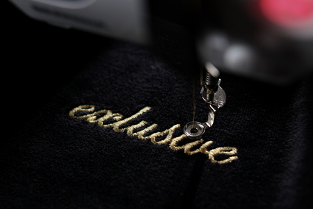 Foto de embroidery of gold lettering exclusive on black velvety fabric with embroidery machine - diagonal view with part of machine - background and foreground blanked out blurry - Imagen libre de derechos