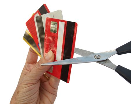 Four credit cards held in a hand, being cut up with pair of scissors.