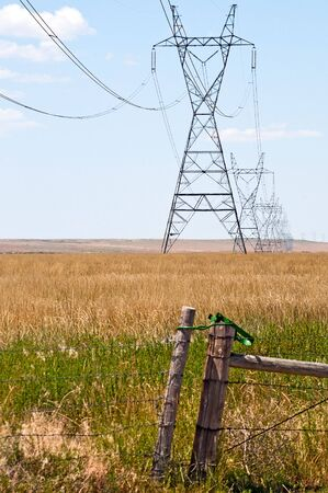 Power lines carrying electric power across the prairie.