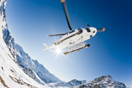 Heli Skiing Helicopter is landing on a ski slope in Gressoney Ski Resort, Aosta, Italy.
