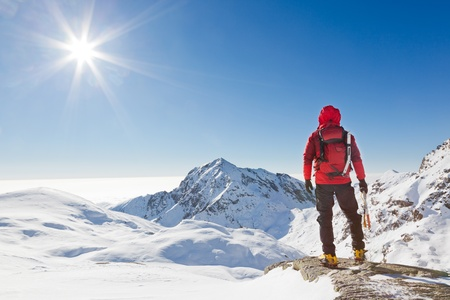Climber looking at a snowy mountain landscape in a sunny winter day   Western Alps, Biella, Italy