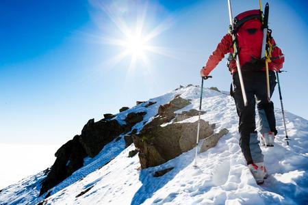 Foto de Mountaineer walking up along a steep snowy ridge with the skis in the backpack. - Imagen libre de derechos