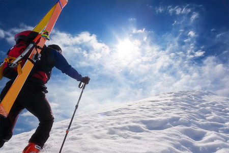 Ski mountaineer walking up along a steep snowy ridge with the skis in the backpack. In background a dramatic sky with a shiny bright sun. Concepts: adventure, achievement, courage, determination, self-realization, dangerous activity, extreme sport, winter