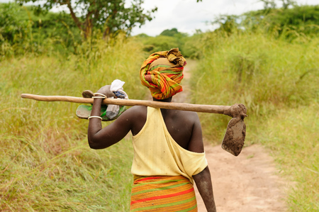 Photo for African woman going to work with the hoe in field - Royalty Free Image