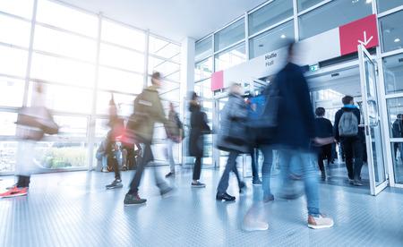 Photo pour Blurred people walking at a trade fair entrance - image libre de droit