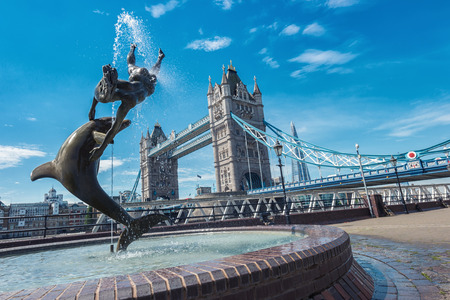 Foto de Tower Bridge and statue of a girl playing with dolphin at St Katharine docks in London. - Imagen libre de derechos