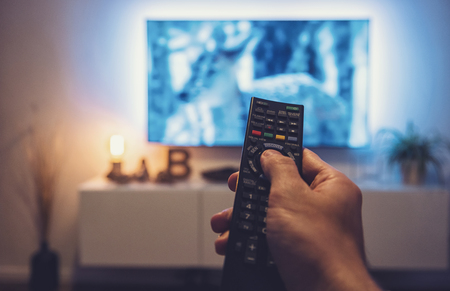 Photo for man Watching movie and using remote control - Royalty Free Image