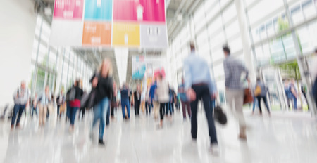 Photo pour Intentionally blurred people walking trade show floor - image libre de droit