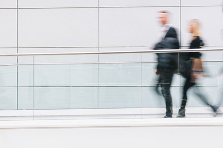 Foto de blurred business people walking in a futuristic corridor, including copy space - Imagen libre de derechos