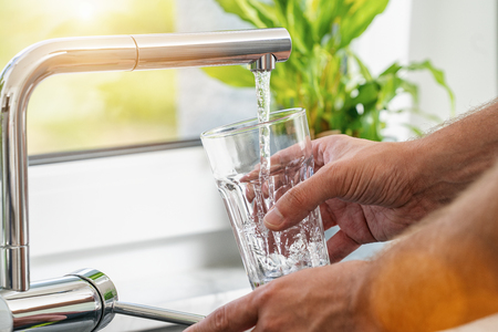 Photo pour Closeup shot of a man pouring a glass of fresh water from a kitchen faucet - image libre de droit
