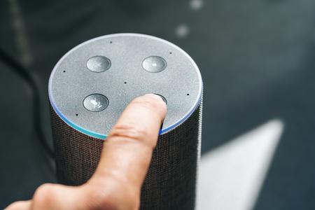 Foto de finger touching voice controlled smart speaker - Imagen libre de derechos