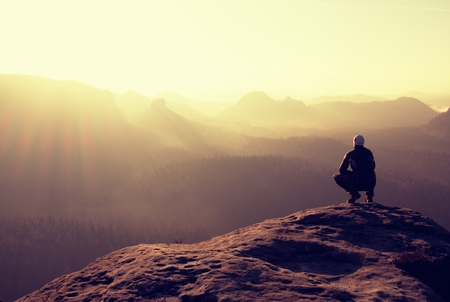 Foto de Hiker sits on a rocky peak and enjoy the scenery - Imagen libre de derechos